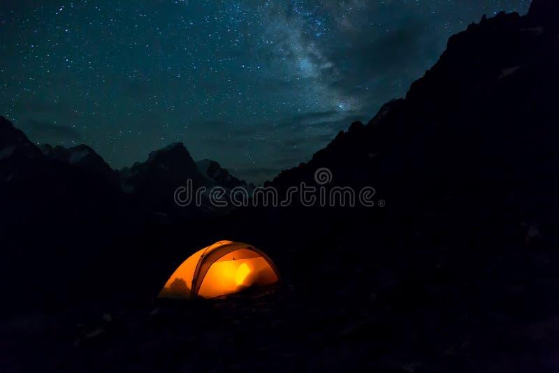 Paysage de montagne de nuit avec la tente lumineuse photos libres de droits
