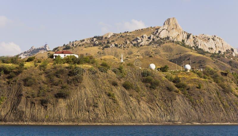 Paysage de montagne : maison et station radar sur la côte image libre de droits