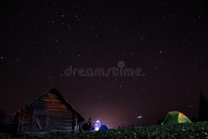 Paysage de montagne de nuit avec la tente lumineuse maison en bois et ciel étoilé photo libre de droits