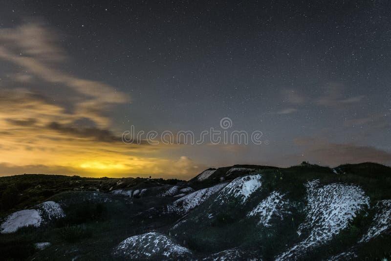 Paysage de nuit avec des arêtes de craie sous le ciel nuageux et étoilé photos stock
