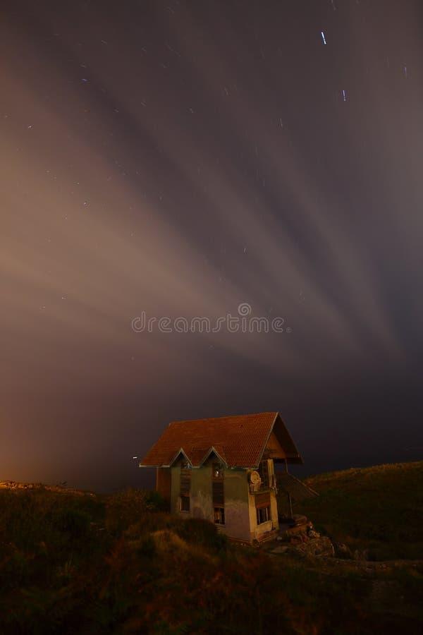 Paysage de nuit de montagne du b?timent ? la for?t la nuit avec la maison de campagne de lune ou de vintage la nuit avec des nuag image stock