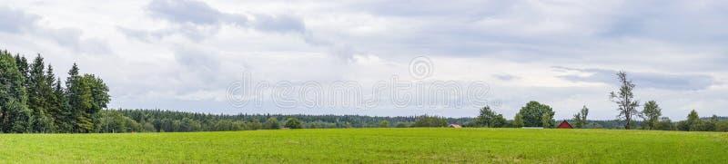 Paysage de panorama avec une grange rouge sur un champ vert photographie stock