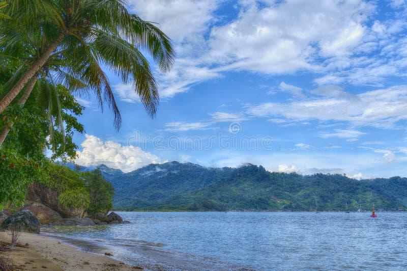 Paysage de plage avec les roches, la colline, les arbres, le ciel bleu, le nuage et la balise photo libre de droits