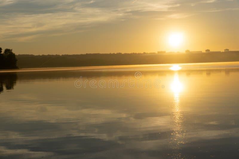 Paysage de premier ressort au lever de soleil de matin sur la rivière Lumières lumineuses du soleil par des arbres sur l'horizon  illustration libre de droits