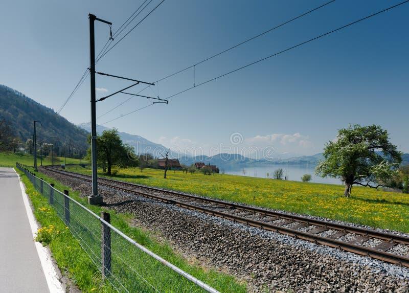 Paysage de ressort avec le lac et les montagnes et les voies de train dans le premier plan photographie stock libre de droits