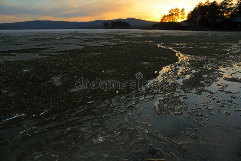 Paysage de ressort sur un lac avec les rivages de fonte le soir image libre de droits
