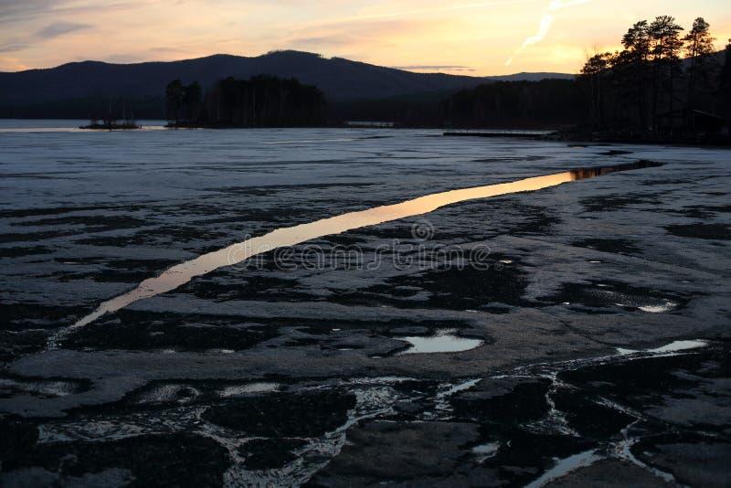 Paysage de ressort sur un lac avec les rivages de fonte le soir photo stock