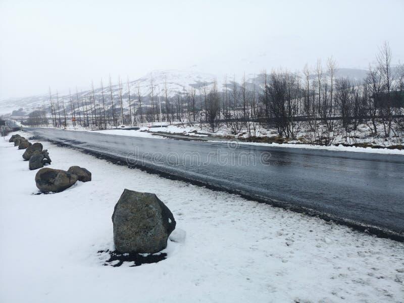 Paysage de route de colline en hiver chez l'Islande Route goudronn?e avec en longueur compl?tement de neige photographie stock libre de droits