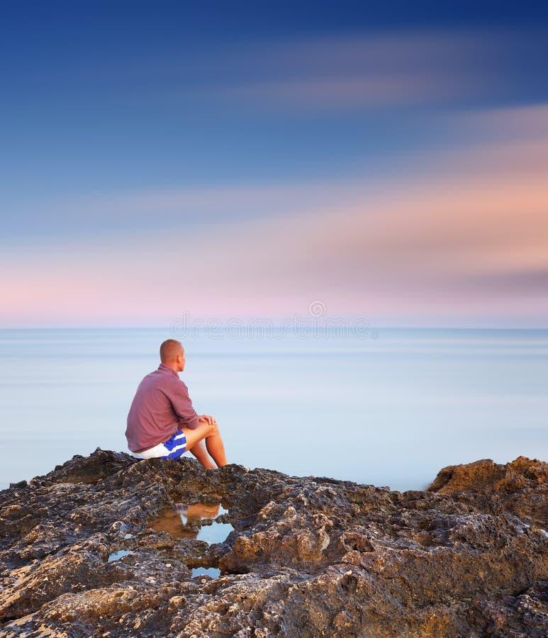 Équipez se reposer sur une roche par la mer images libres de droits