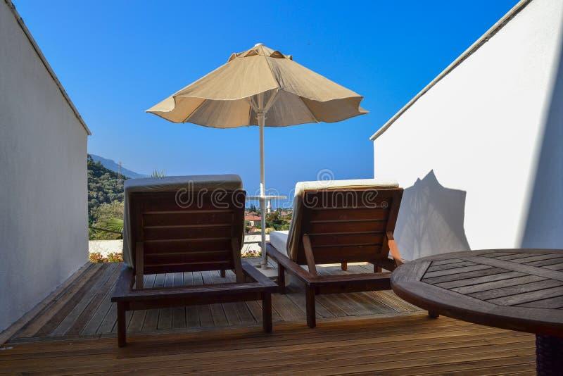 Paysage de station de vacances - parapluies de plage et salons de cabriolet dans la perspective de la côte Turquie Oludeniz photo libre de droits
