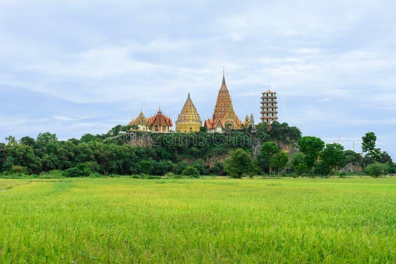 Paysage de Tiger Cave Temple ou de Wat Tham Sua avec le champ vert et le ciel bleu, Kanchanaburi, Thaïlande photo stock