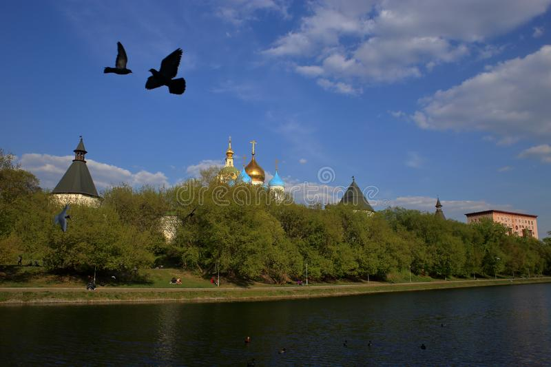 Paysage de ville avec les oiseaux de vol et le monastère de Novospassky images stock