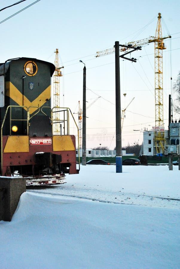 Paysage de ville de Kharkiv avec la grue de support à la construction de l'immeuble dans l'horizon, petit vieux train vert d'entr photos libres de droits