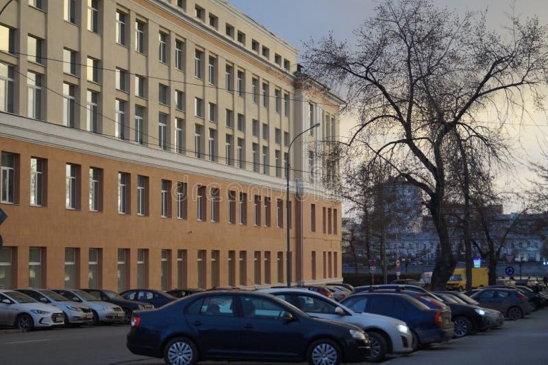 Paysage de ville de ressort : un nouveau bâtiment classique, rue 17 de Pervomayskaya, illuminée par la lumière de coucher du sole photographie stock libre de droits