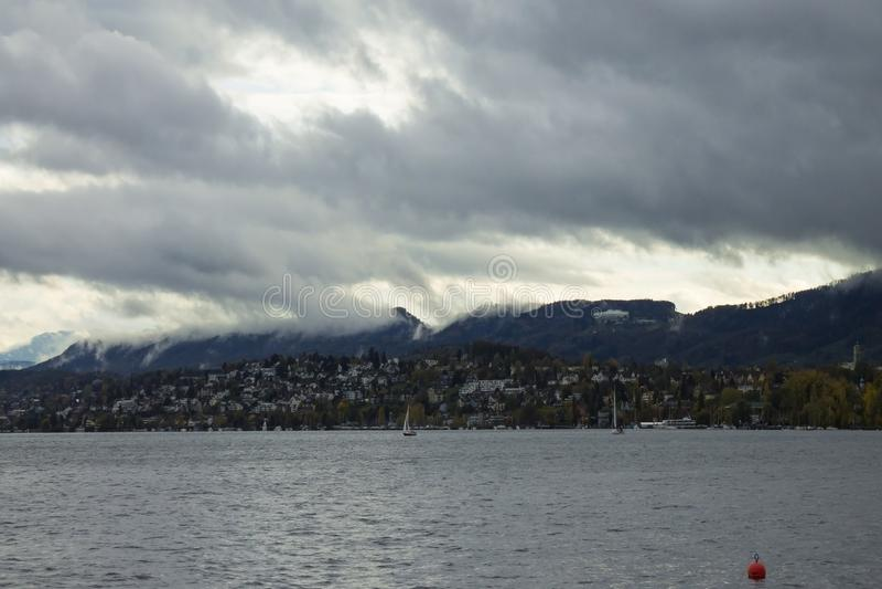 Paysage de Zurich de lac Ciel nuageux avec les crêtes de montagnes couvertes par neige d'Alpes sur l'horizon photographie stock libre de droits