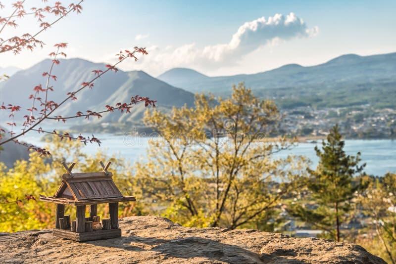 Paysage idyllique au Japon avec la maison en bois traditionnelle de jouet et le beau lac avec des montagnes au fond photographie stock libre de droits