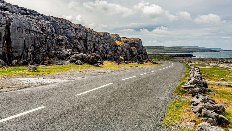 Paysage irlandais le long du Burren avec la route R477 côtière rurale et la mer à l'arrière-plan image stock
