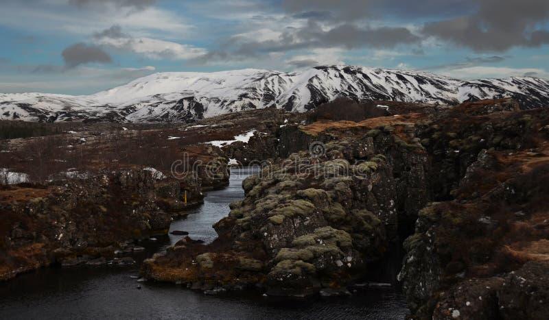 Paysage islandais typique : Le parc national de Thingvellir, rivières, gisements de lave a couvert de neige contre le contexte de photos stock
