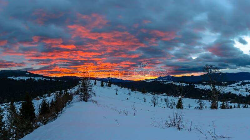 Paysage magnifique des montagnes carpathiennes à l'aube avec les nuages rouges lumineux photographie stock libre de droits