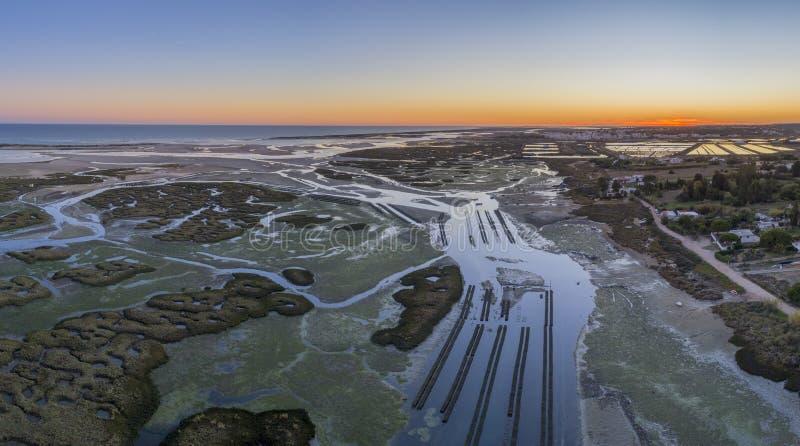 Paysage marin aérien de crépuscule de production d'huître, en marécages de Ria Formosa, Algarve image libre de droits