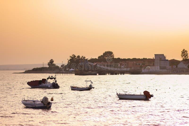 Paysage marin avec des bateaux flottant sur la mer avec la ville de Gerakini au coucher du soleil image libre de droits