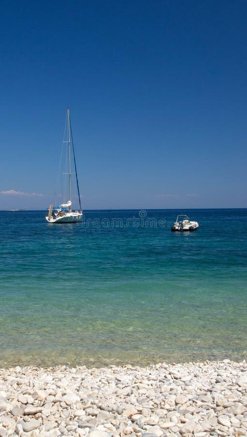 Paysage marin avec l'obtention du diplôme bleue et le bateau à voile ancré photos libres de droits