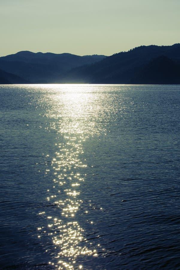 Paysage marin crépusculaire Montagnes et reflet du soleil dans l'eau photographie stock libre de droits