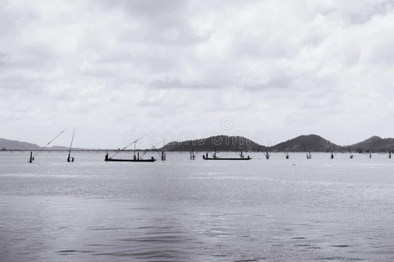 Paysage marin de baie de Songkhla dans la saison d'été avec le pêcheur sur des bateaux de pêche avec de longues cannes à pêche photos stock