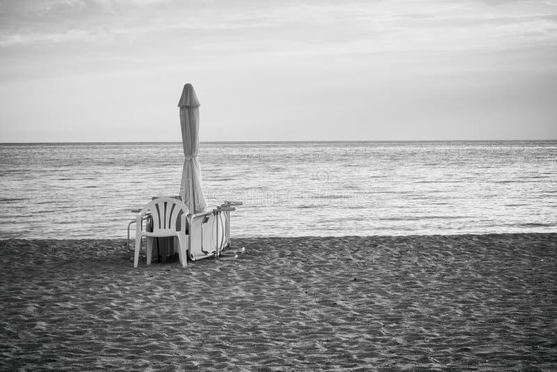 Paysage marin de matin, solitude, accessoires de plage - parapluie, canapé et chaise sur la plage sablonneuse photos stock
