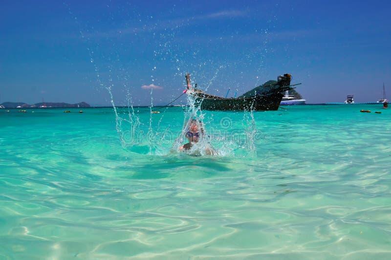 Paysage marin de paradis Petit garçon éclaboussant en mer tropicale chaude de l'eau de turquoise le jour ensoleillé contre le cie photos stock