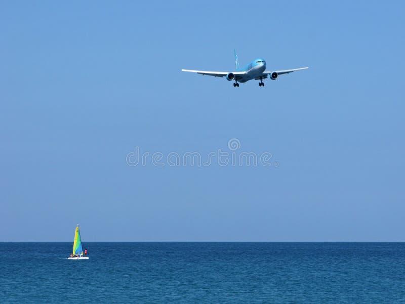 Paysage marin : voilier vibrant et avion au-dessus de mer photo stock