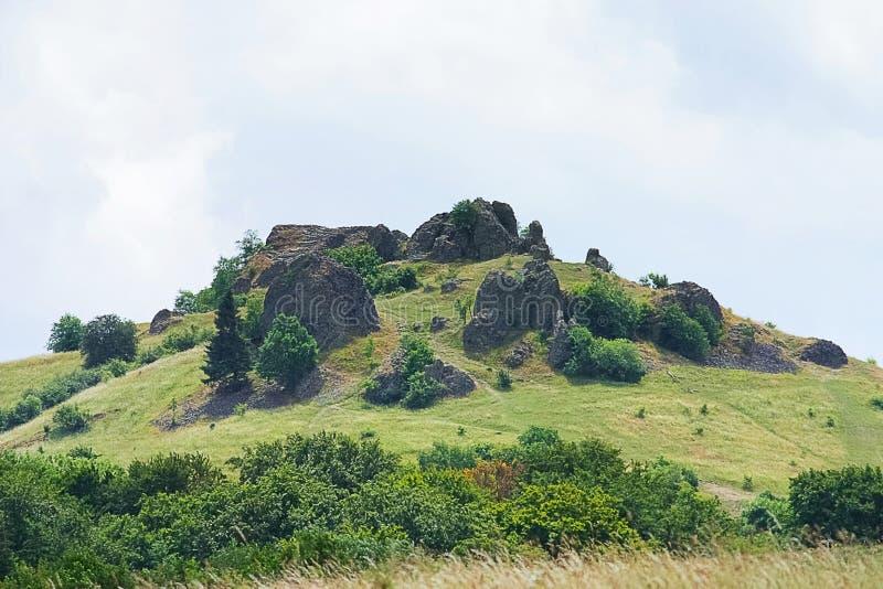Paysage mystérieux de colline avec des roches, des prés et des arbres photo libre de droits