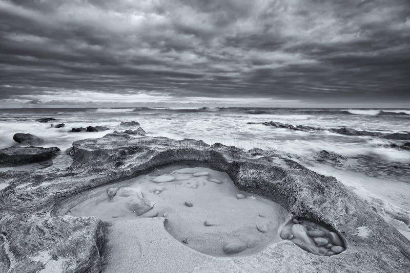 Paysage noir et blanc des roches d'océan et de l'escroquerie artistique de nuages image libre de droits