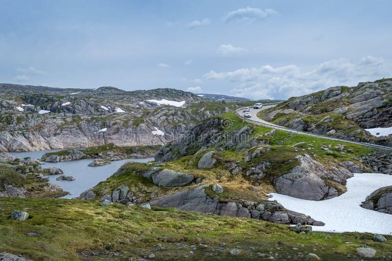 Paysage norvégien scénique avec les roches, le lac et la route incurvée de montagne photo stock