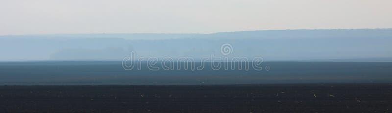 Paysage panoramique abstrait avec une image de sol, de brouillard, de forêt et de ciel par temps nuageux chaud au printemps image stock