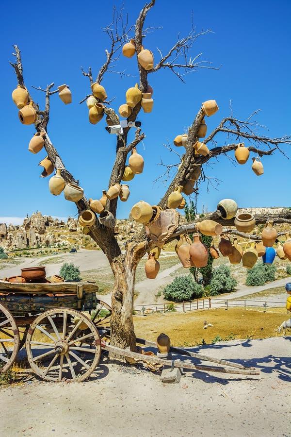 Paysage pittoresque avec des cruches sur un arbre et un vieux chariot complètement des pots d'argile photographie stock libre de droits