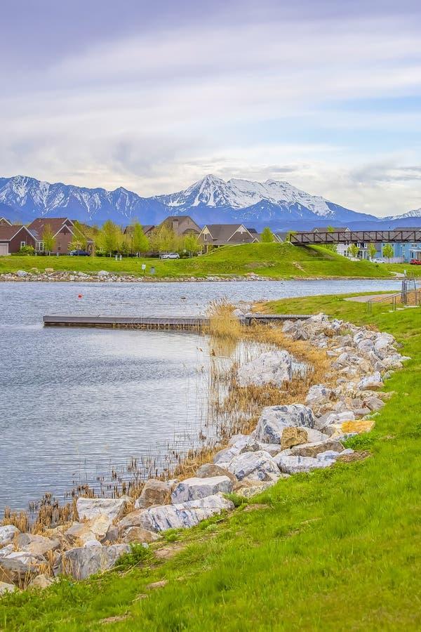 Paysage pittoresque de lac avec la plate-forme et les roches en bois sur le rivage herbeux images libres de droits