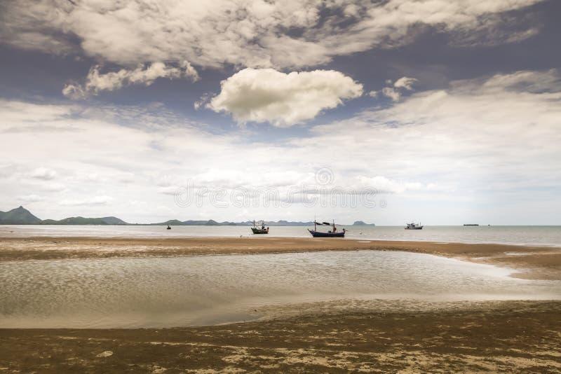 Paysage pittoresque stupéfiant avec la plage, les bateaux de pêcheur et le ciel nuageux image libre de droits