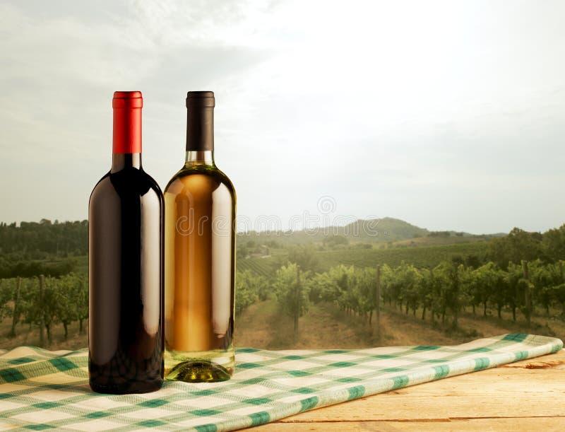 Paysage rural avec des bouteilles de vin sur le premier plan image libre de droits
