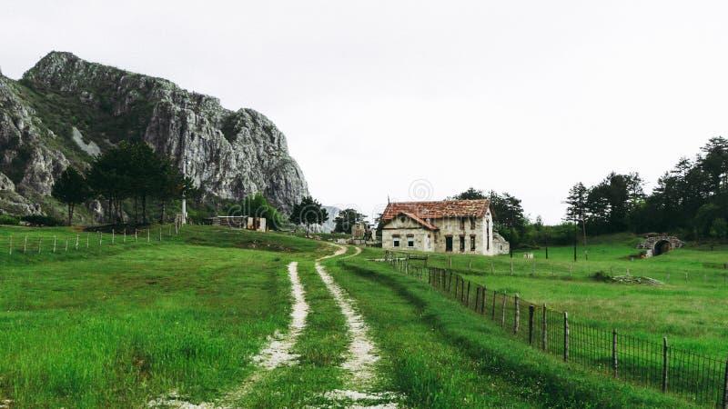 Paysage rural avec la maison de campagne de la ferme locale apr?s les for?ts vertes de montagne Une route scénique par le village photo libre de droits