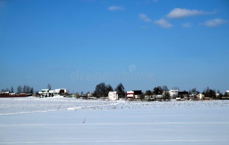Paysage rural avec un village sur l'horizon après champ de neige sous le ciel sans nuages bleu clair le jour ensoleillé lumineux photographie stock libre de droits