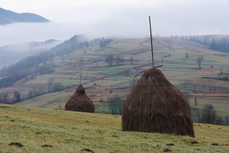 Paysage rural avec une pile de foin sec dans le domaine de la montagne photos libres de droits