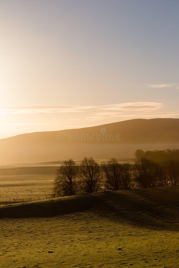 Paysage rural brumeux de montagnes dans la lumière de lever de soleil image libre de droits