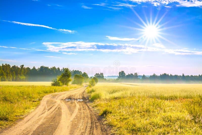 Paysage rural d'été avec un champ, un lever de soleil et une route photos stock