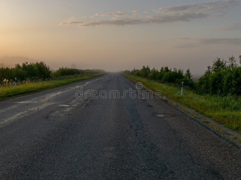 Paysage rural dans la brume de matin, route vide, image stock