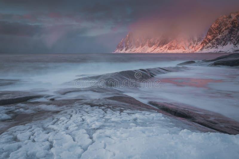 Paysage stupéfiant sur des îles de Lofoten pendant le coucher du soleil, les montagnes, la neige et l'eau en Norvège image libre de droits