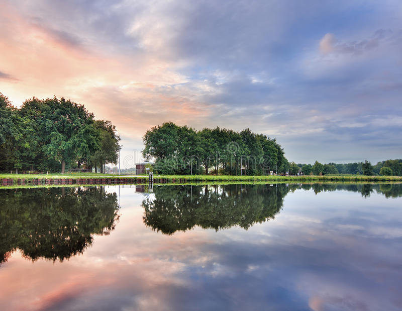 Paysage tranquille avec un canal, des arbres, un ciel multicolore et des nuages dramatiques, Tilburg, Pays-Bas photo libre de droits