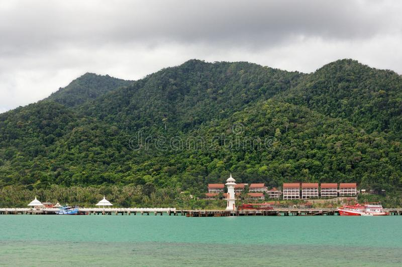 Paysage tropical avec la mer tropicale de turquoise, le phare blanc, le bateau de pêche, le pilier de Bao de coup et l'île de Koh images stock