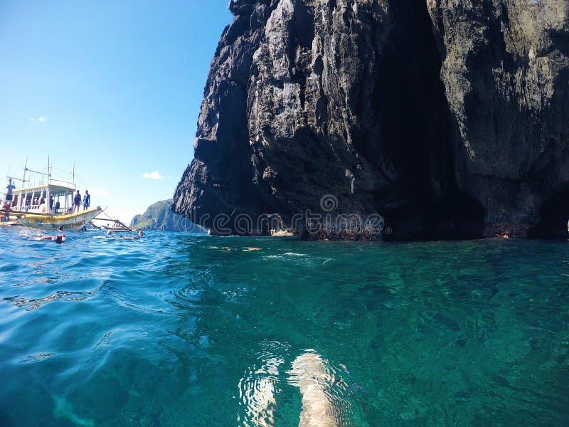 Paysage tropical d'île avec la mer et la montagne Bain de touristes en mer bleue près de caverne Tache guidée de visite de bateau photographie stock libre de droits