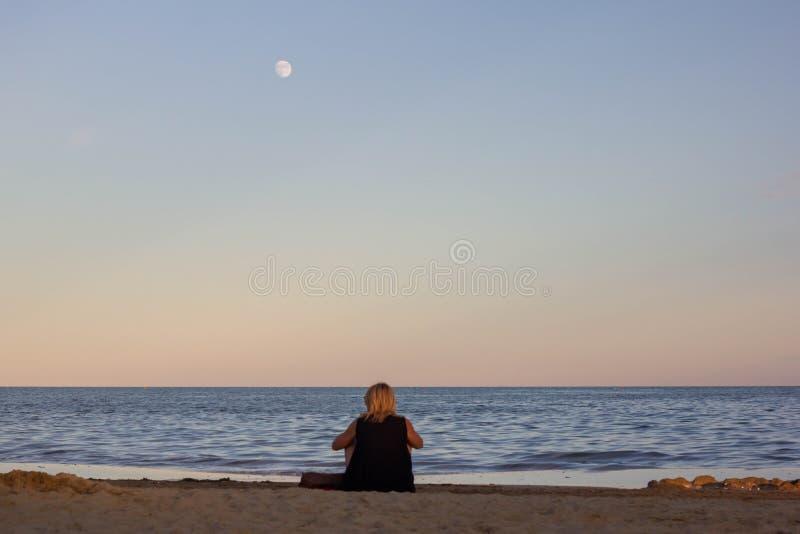 Paysage une belle mer, sable, la lumière du soleil affaibli avec l'arrivée du coucher du soleil et une femme qui observe tout cec image libre de droits